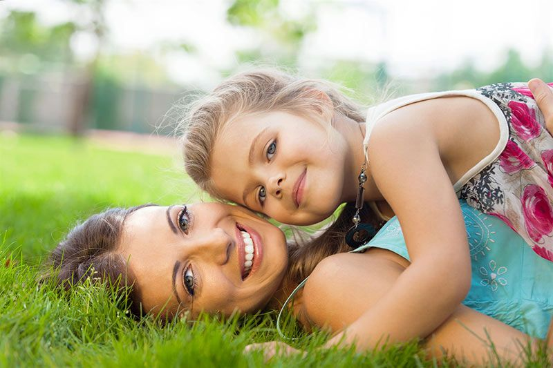 mother and daughter snuggle on beautiful lawn